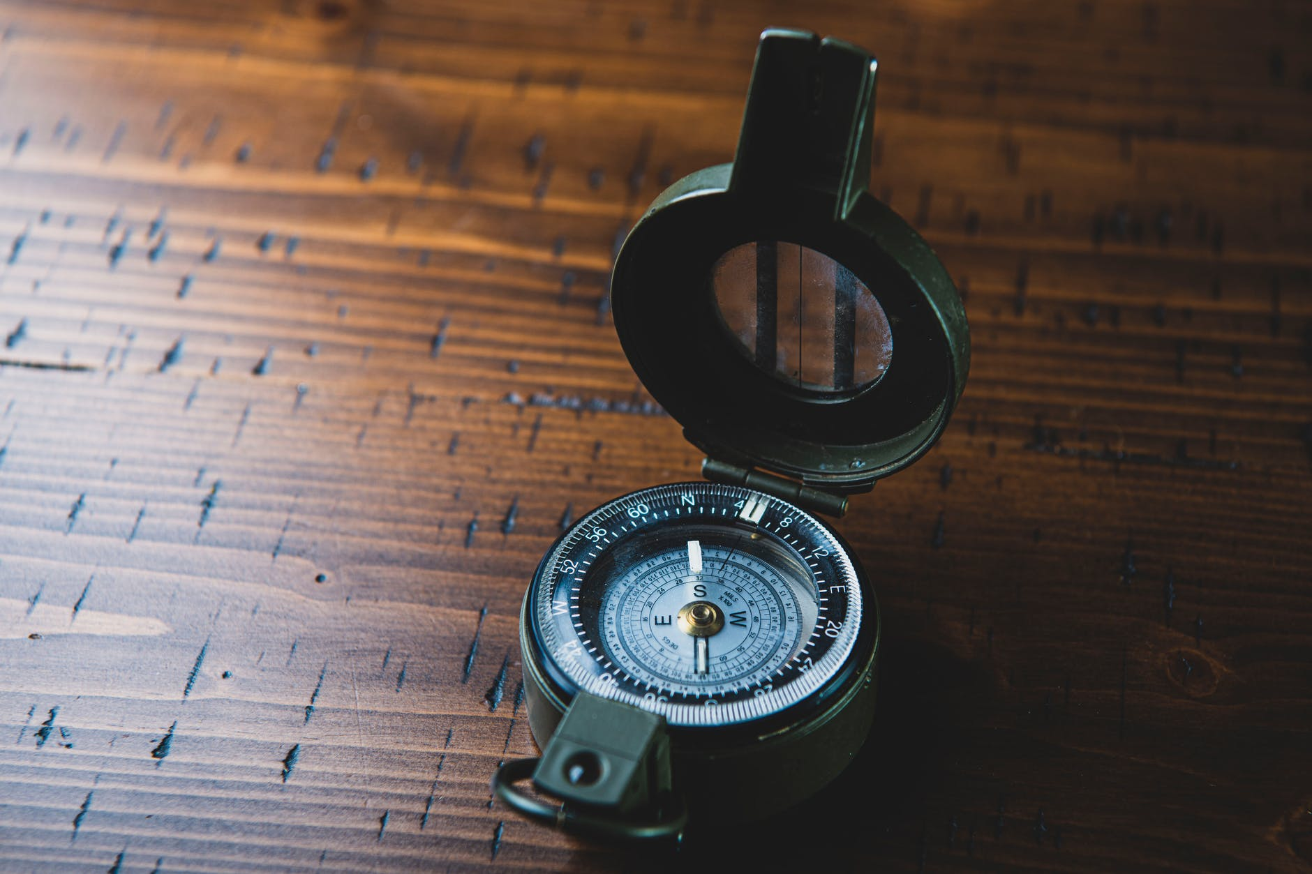 compass on brown wooden table